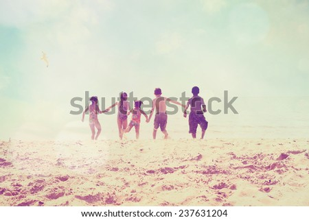 kids running at the beach, defocused image.  Focus on sand. Instagram effect. - stock photo