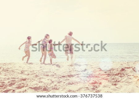 kids running at the beach, runners are blurred, focus on sand in foreground, Instagram toned