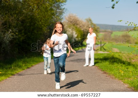 kids running down a path in spring, their pregnant mother standing in the background - stock photo