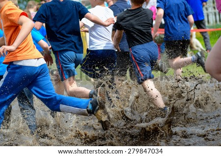 Kids running trail race, legs in mud and water  - stock photo
