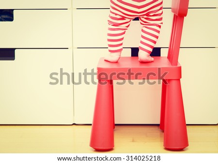 kids safety concept- little girl  climbing on baby chair - stock photo