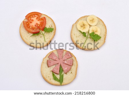 Kids sandwiches in the shape of flowers of tomatoes, sausage, cheese and parsley  - stock photo