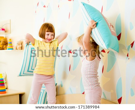 kids sisters playing with pillows in the bedroom - stock photo