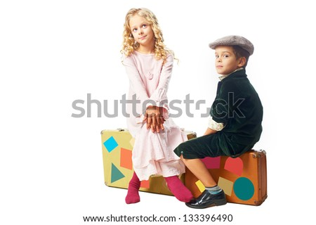 Kids sitting on a suitcases on white background - stock photo