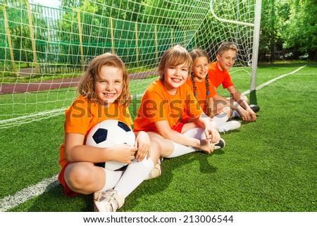 Kids sitting together on field near woodwork