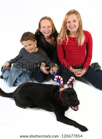 Kids sitting with the family dog wearing Christmas hat - stock photo