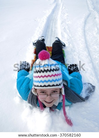 Kids sledding down snowy hill on sled fast speed - stock photo