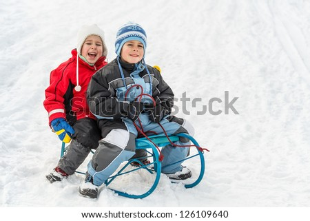 Kids sliding in the snow - stock photo