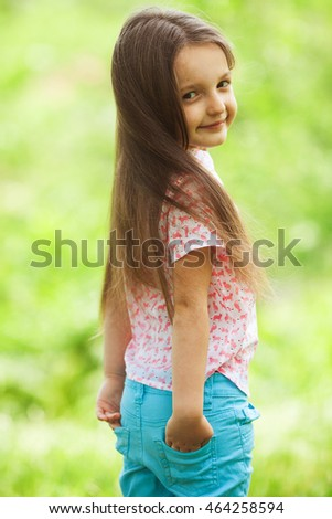 Kids street fashion concept. Portrait of funny and sweet little girl with long light brown hair. Trendy casual look. Hands in pockets. Outdoor shot