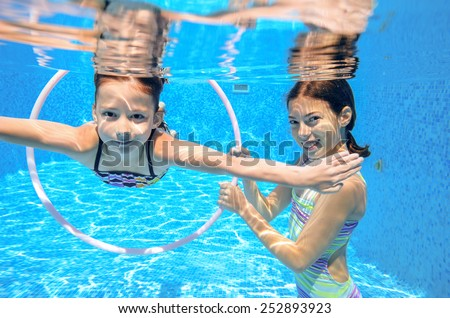 Kids swim in pool underwater, girls swimming, playing and having fun, children water sport