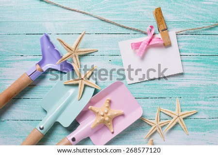 Kids tools for playing in sand  and sea object on turquoise  painted wooden planks. Place for text. Vacation, holiday, summer background. - stock photo
