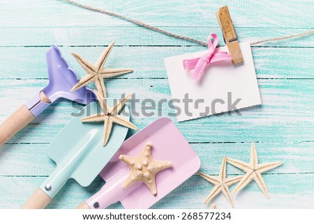 Kids tools for playing in sand  and sea object on turquoise  painted wooden planks. Place for text. Vacation, holiday, summer background. Toned image. - stock photo