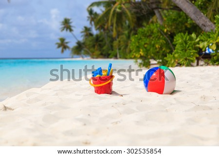 kids toys on tropical sand beach, family vacation - stock photo