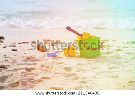 kids toys on tropical sunset beach - stock photo
