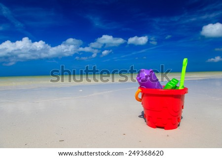 kids toys on white sand beach, playing on vacation - stock photo