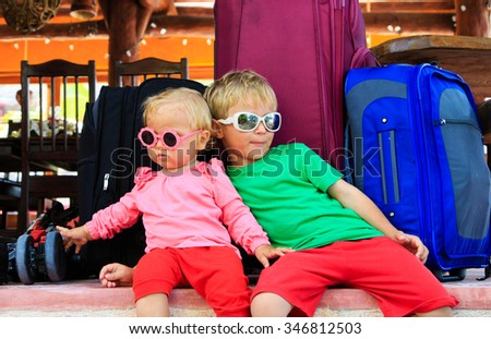 kids travel concept- little boy and toddler girl sitting on suitcases ready to travel