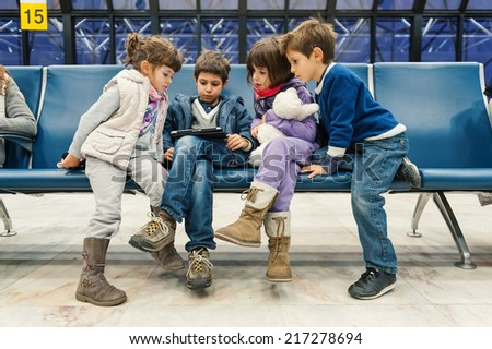 Kids waiting for flight inside Lisbon airport. Portela Airport is an international airport in the city of Lisbon, it opened on 1942 and had reached 100,000 passengers.  - stock photo