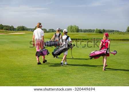 Kids walking on fairway with bags at golf school, back view - stock photo