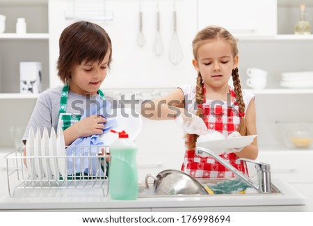 Kids washing the dishes in the kitchen together - helping out with the home chores - stock photo