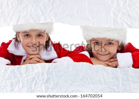Kids watching the unwrapping christmas present - looking through torn paper strip, copy space - stock photo