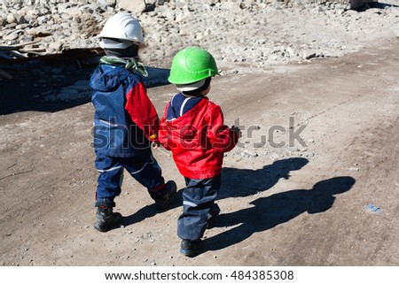 Kids wearing protective helmets, waking to a construction site