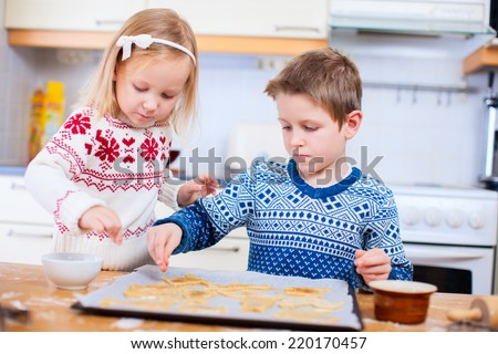 Kids wearing warm sweaters baking cookies in house kitchen on winter day