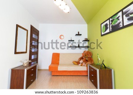 Kids white and green bedroom with orange sofa