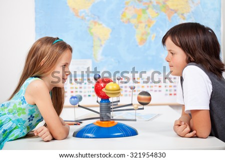 Kids with a scale model planetary system in geography science class discussing - stock photo