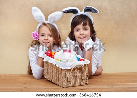 Kids with bunny ears and easter basket - copy space on golden background - stock photo