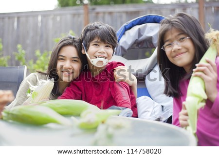 Kids with disabled brother peeling husk off ears of corn - stock photo