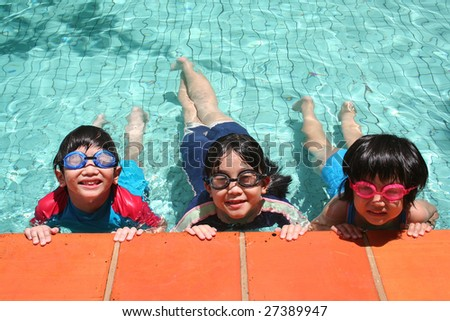 Kids with goggles in the pool on sunny day