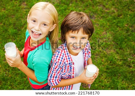 Kids with milk moustaches. Top view of two cute little children with milk moustaches holding glasses with milk and smiling while standing on green grass together  - stock photo