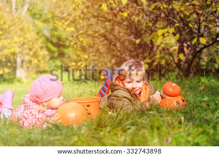 kids with pumpkin and halloween toys play at autumn park, kids trick or treating - stock photo