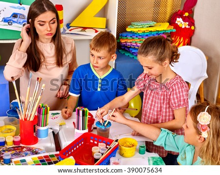 Kids with teacher woman painting on paper at table  in  kindergarten school. Painting school.