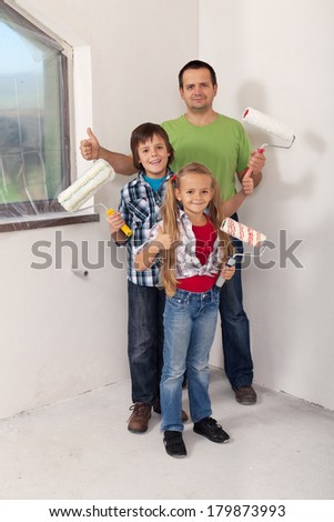 Kids with their father preparing to paint the room in their new home - redecorating concept