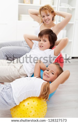 Kids with their mother doing gymnastic exercises with large balls at home