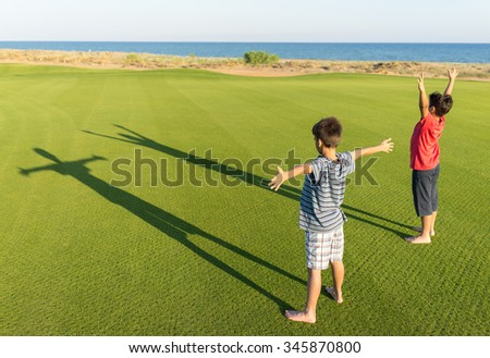 Kids with their shadows on grass - stock photo