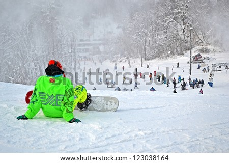 KIEV-DEC 22: Young sportsman in green suite with snowboard in Protasov Yar in Kiev, Ukraine on December 22,2012. Protasov Yar provide 2 downhill route (300m and 500m) for downhill skiing European Cup. - stock photo