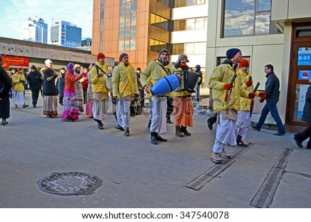 KIEV - MAR 05: Hare Krishna people group with drum and harmonic dancing and singing on the street in Kiev, Ukraine on March 05, 2013.