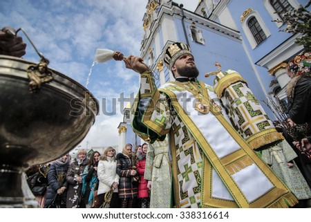 Kiev, Ukraine - April 5, 2015: An Orthodox Church priest blesses the faithful holding willow twigs during a mass to mark the Orthodox Christian Palm Sunday in Kiev. - stock photo