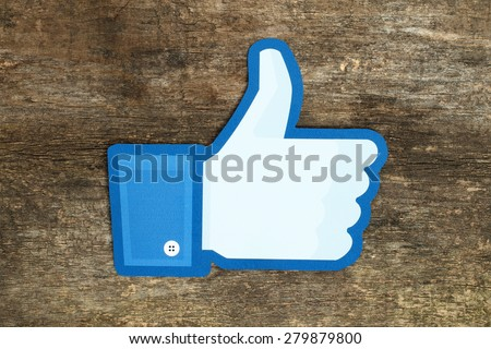 KIEV, UKRAINE - APRIL 15, 2015: Facebook thumbs up sign printed on paper and placed on wooden background. Facebook is a well-known social networking service. - stock photo