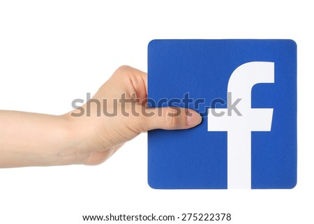 KIEV, UKRAINE - APRIL 30, 2015: Hand holds facebook logo printed on paper on white background. Facebook is a well-known social networking service. - stock photo