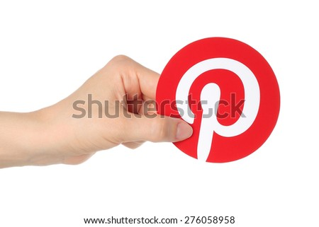KIEV, UKRAINE - APRIL 30, 2015:Hand holds Pinterest logotype printed on paper. Pinterest is photo sharing website - stock photo