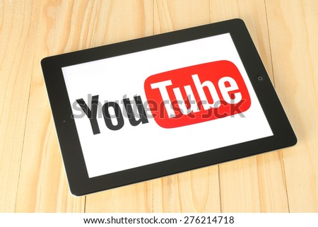 KIEV, UKRAINE - APRIL 30, 2015: YouTube logotype on iPad screen on wooden background. YouTube is a video-sharing website. - stock photo