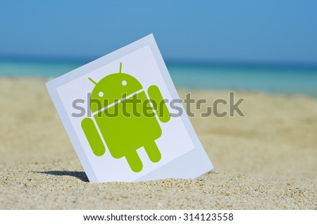 KIEV, UKRAINE - AUGUST 10, 2015: Android logotype printed on paper and placed in the sand against the sea. Android - the operating system for smart phones, tablet computers, e-books, game consoles. - stock photo