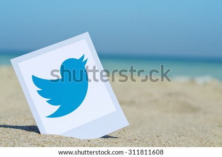KIEV, UKRAINE - AUGUST 10, 2015: Twitter logotype printed on paper  and placed in the sand against the sea. Twitter social network for public exchange of short messages. - stock photo