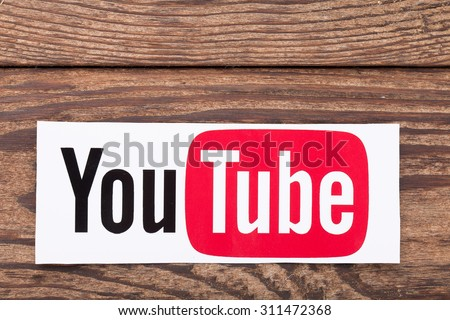 KIEV, UKRAINE - AUGUST 22, 2015: YouTube logotype button printed on paper and lies on wooden background. YouTube is video-sharing website. The service was created by in February 2005. - stock photo