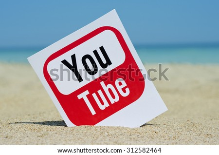 KIEV, UKRAINE - AUGUST 10, 2015:  YouTube logotype  printed on paper and placed in the sand against the sea. YouTube is the popular online video-sharing website. - stock photo