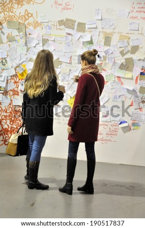 KIEV, UKRAINE - CIRCA APRIL 2014: Unknown people read advertisements on the art and book exhibition in Arsenal museum on April 2014 in Kiev, Ukraine