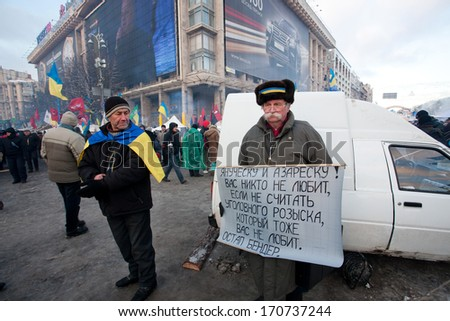 KIEV, UKRAINE - DEC 10: Demonstrators with national symbols and banners call for president to resign on the main square during anti-government protest Euromaidan on December 10, 2013 in Kyiv, Ukraine